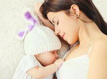 Madre del primo piano del ritratto giovane che dorme con il bambino sul letto a casa immagini stock