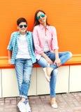 Madre del ritratto ed adolescente del figlio che indossa una camicia a quadretti e gli occhiali da sole Fotografie Stock