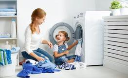 Madre della famiglia ed assistente del bambino piccolo nella stanza di lavanderia vicino al washi fotografia stock libera da diritti