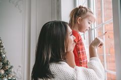 Madre di amore che gioca con la sua neonata che esamina la finestra immagini stock libere da diritti