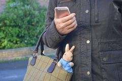 Madre di funzionamento, con un giocattolo del ` s del bambino che attacca dalla sua borsa fotografie stock libere da diritti