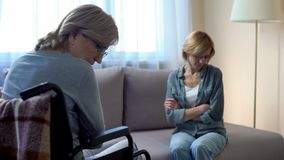 Madre discapacitada mayor que habla con la hija trastornada, problemas de la familia, pelea imágenes de archivo libres de regalías
