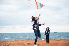 Madre divertente e bambino che giocano con un aquilone contro lo sfondo del mare in tempo nuvoloso Fotografia Stock