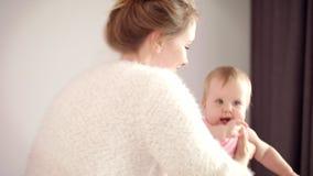 Madre dulce con el pequeño bebé en las manos Sonrisa alegre de la mujer para embromar a la muchacha almacen de metraje de vídeo