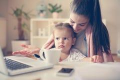 Madre e bambina a casa facendo uso del computer portatile insieme immagine stock
