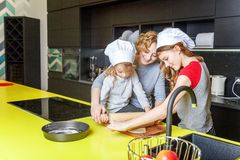 Madre e bambini che cucinano nella cucina e nel divertiresi immagine stock libera da diritti