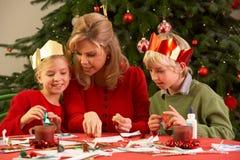 Madre e bambini che fanno le cartoline di Natale Immagini Stock