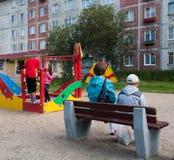 Madre e bambini che giocano sul campo da giuoco nell'iarda Fotografia Stock