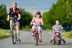 Madre e bambini che guidano una bicicletta Fotografie Stock