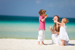 Madre e bambini che hanno divertimento sulla spiaggia Fotografie Stock Libere da Diritti