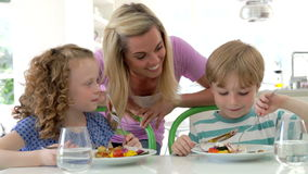 Madre e bambini che mangiano pasto a casa insieme stock footage