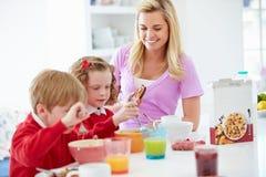 Madre e bambini che mangiano prima colazione in cucina insieme Fotografie Stock Libere da Diritti