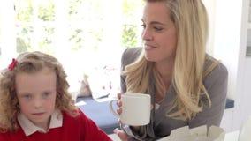 Madre e bambini che mangiano prima colazione in cucina insieme video d archivio
