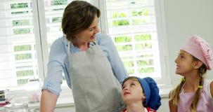 Madre e bambini che producono i biscotti in cucina archivi video