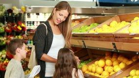 Madre e bambini che selezionano frutta in supermercato archivi video