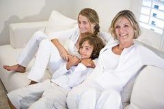 Madre e bambini che si distendono sul sofà bianco immagine stock libera da diritti