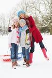 Madre e bambini che tirano slitta attraverso la neve Fotografie Stock