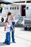 Madre e bambini davanti all'aeroplano immagine stock