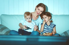 Madre e bambini della famiglia che guardano televisione a casa Fotografia Stock Libera da Diritti