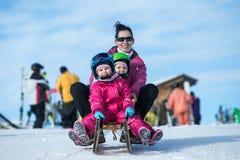 Madre e bambini divertendosi sulla slitta con la vista panoramatic delle montagne delle alpi La mamma attiva ed il bambino scherz immagine stock