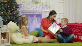 Madre e bambini felici con il regalo di Natale vicino all'albero di Natale a casa archivi video