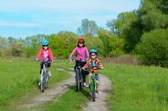 Madre e bambini felici sulle bici che ciclano all'aperto Immagini Stock