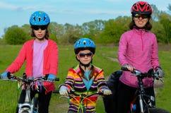 Madre e bambini felici sulle bici che ciclano all'aperto Immagine Stock Libera da Diritti
