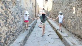 Madre e bambini in rovine della città antica di Pompei vicino al vulcano Vizuvius, Pompei, Napoli, Italia archivi video