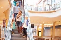 Madre e bambini sulla scala mobile nel centro commerciale fotografia stock