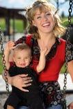 Madre e bambino all'oscillazione del campo da giuoco Immagine Stock Libera da Diritti