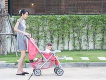 Madre e bambino asiatici in passeggiatore, sulla via in villaggio Immagini Stock