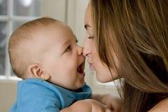 Madre e bambino che baciano e che ridono Immagine Stock