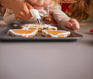 Madre e bambino che decorano i biscotti di natale con la glassa Immagine Stock Libera da Diritti