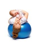 Madre e bambino che fanno gli esercizi relativi alla ginnastica sulla palla Fotografia Stock Libera da Diritti