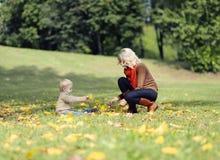Madre e bambino che giocano in autunno Fotografie Stock