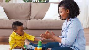 Madre e bambino che giocano con i blocchetti del giocattolo a casa archivi video