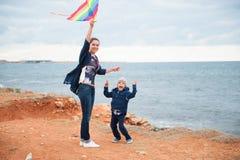 Madre e bambino che giocano con un aquilone contro lo sfondo del mare in tempo nuvoloso Immagini Stock Libere da Diritti