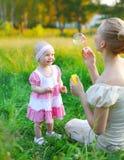 Madre e bambino che giocano le bolle di sapone di salto sull'erba Fotografia Stock