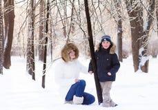 Madre e bambino che giocano nella neve profonda sul tramonto Fotografia Stock