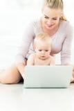 Madre e bambino che per mezzo del computer portatile Immagini Stock