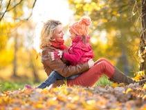 Madre e bambino che si siedono insieme e che abbracciano in autunno Immagini Stock Libere da Diritti