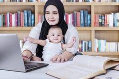 Madre e bambino che utilizza computer portatile nella biblioteca immagini stock libere da diritti
