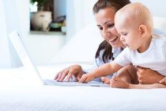 Madre e bambino con il computer portatile Immagini Stock