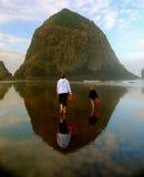 Madre e bambino con il secchio rosso sulla spiaggia riflettente Fotografia Stock