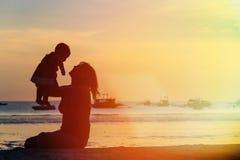 Madre e bambino felici alla spiaggia di tramonto Immagini Stock Libere da Diritti
