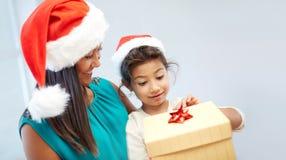 Madre e bambino felici in cappelli di Santa con il contenitore di regalo Immagini Stock