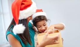 Madre e bambino felici in cappelli di Santa con il contenitore di regalo Fotografia Stock Libera da Diritti