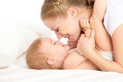 Madre e bambino felici della famiglia divertendosi gioco, ridente sul letto Immagine Stock