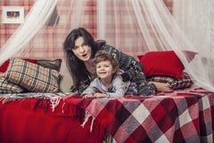 Madre e bambino felici della famiglia insieme a casa nel atmosp accogliente Immagini Stock