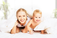 Madre e bambino felici della famiglia sotto le coperte a letto